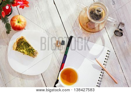 Datebook, pencil, cup of tea, chicken pie, apple, glass teapot and watch on white wooden table
