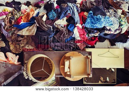 high-angle shot of a pile of different pieces of furniture and some piles of used clothes on sale in a flea market