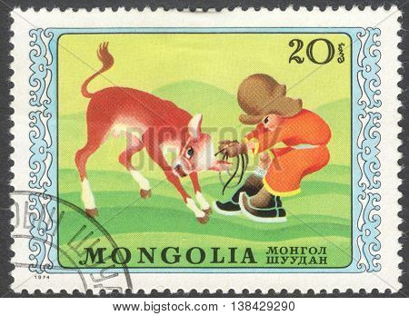 MOSCOW RUSSIA - JANUARY 2016: a post stamp printed in MONGOLIA shows a boy and a cow the series