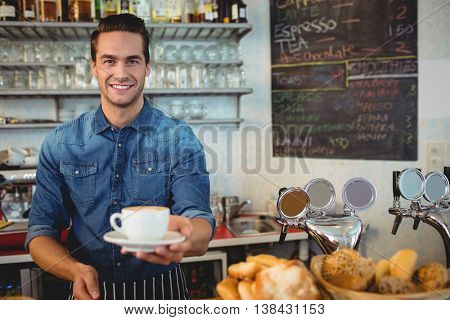 Portrait of happy young owner offering coffee at cafeteria
