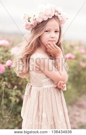 Smiling baby girl 3-4 year old wearing stylish dress and wreath with roses outdoors. Looking at camera. Childhood.