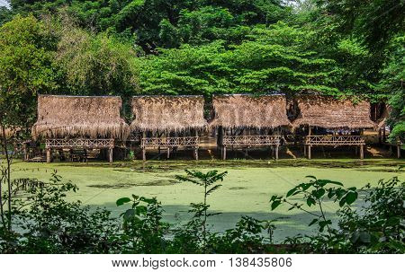 Nipa bamboo Huts at the White Sand beach with palm trees in Raja Ampat, Papua New Guinea, Indonesia