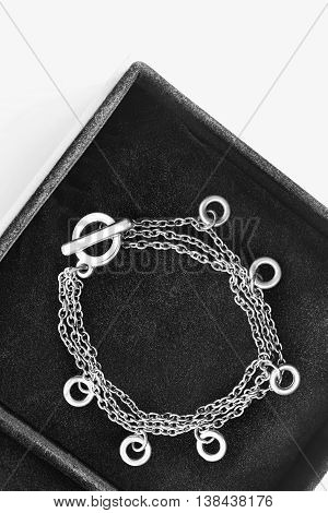 Silver chain bracelet in black jewel box as a background