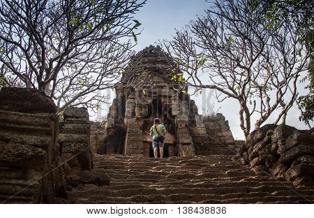 Young female tourist with smartphone taking picture of the gopura under blue sky near the entrance to ancient Preah Khan temple in Angkor. Siem Reap, Cambodia.