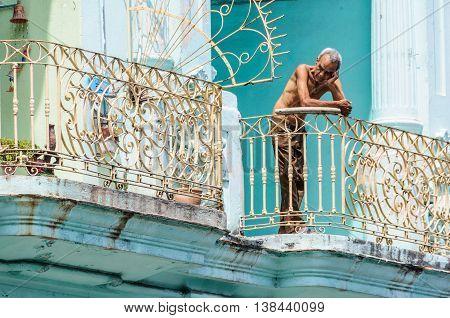 HAVANA, CUBA - MARCH 17, 2016: People on their balcony in Paseo de Marti in Havana the capital of Cuba