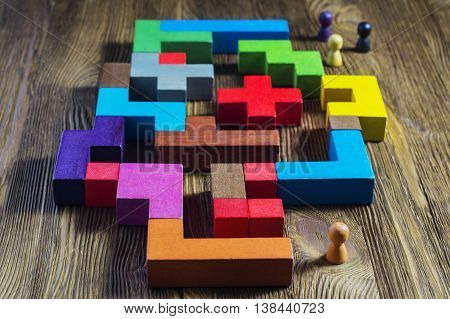 The man in the maze. The concept of a business strategy, analytics, search for solutions, the search output. Labyrinth of colorful wooden blocks, tetris.