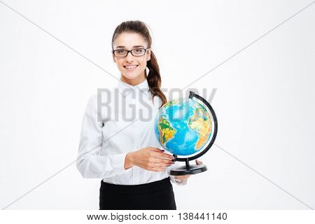 Smiling beautiful young busineswoman in glasses standing and holding globe over white background