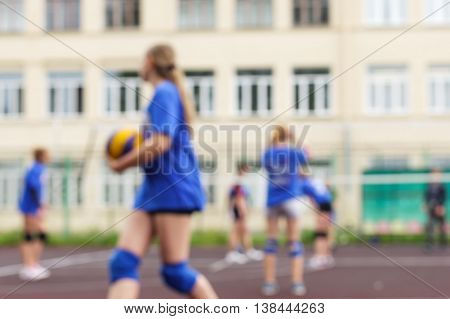 Blurred school girls playing volleyball in the open air.