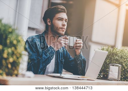 In search of inspiration. Thoughtful young man holding cup of coffee while sitting at sidewalk cafe