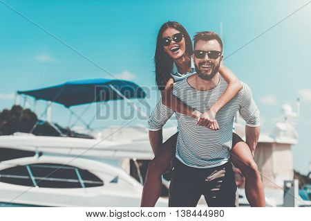 Carefree fun. Happy young man carrying his beautiful girlfriend on shoulders while standing on quay