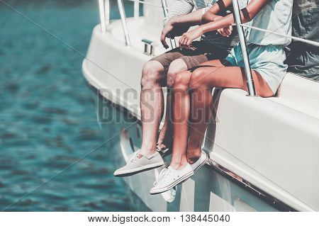 Spending summer day on yacht. Close-up of young couple sitting on the board of yacht