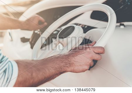Everything is in his hands. Close-up of young man holding hand on steering wheel while driving yacht