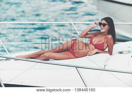 Carefree time on yacht. Beautiful young woman adjusting eyewear and smiling while lying on the deck of yacht