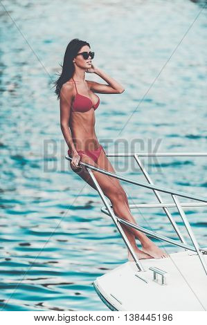 Enjoying her perfect vacation. Beautiful young woman leaning at the handrail and looking away while standing on the ship bow