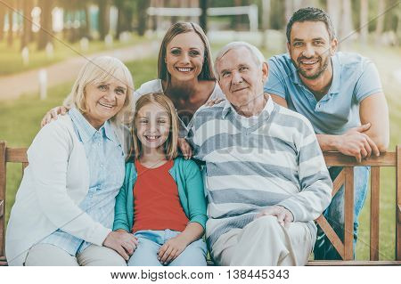 Happy family concept. Happy family of five people bonding to each other and smiling while sitting outdoors together