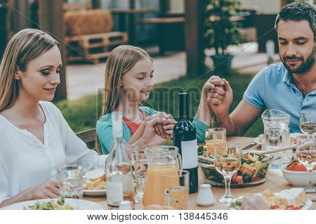 Feeling thankful for meal. Family holding hands and praying before dinner while sitting at the table outdoors