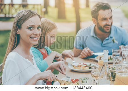 Enjoying dinner with family. Happy family enjoying meal together while woman looking at camera and smiling