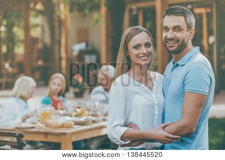 Enjoying time with family. Happy young couple bonding to each other and smiling while their family sitting at the dining table in the background