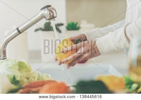 Washing vegetables. Beautiful young woman washing vegetables for salad and smiling while standing in the kitchen