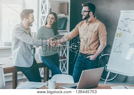 Great job! Confident young man standing near whiteboard and shaking hand to his colleague while young woman standing near them and smiling