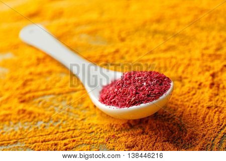 Sumac in white spoon on mixed spices background
