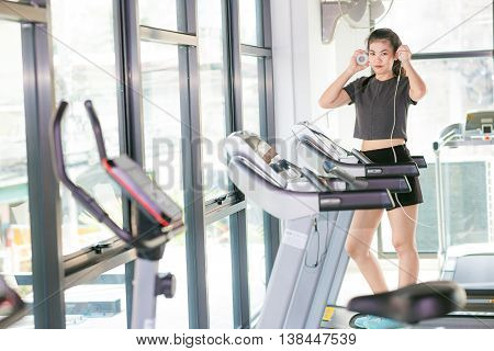 Sport Girl With Headphones Relaxing In The Gym
