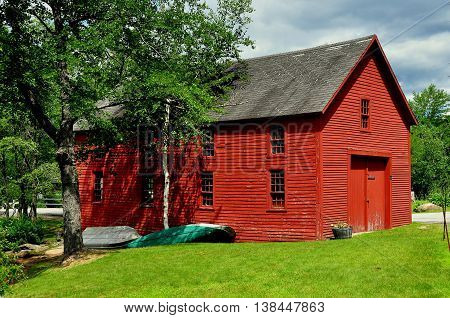 Harrisville, New Hampshire - July 12 2013: Two wooden rowboats lie next to a bright red barn in the village's historic district