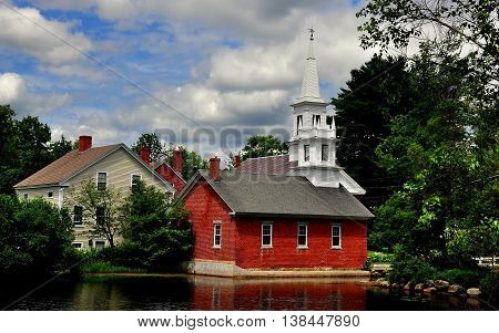 Harrisville New Hampshire - July 11 2013: A quintessential early 196h century New England village with its brick library white steepled church and clapboard house seen across Harrisville Pond