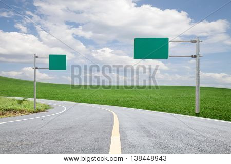 blank green road-sign for your advertisement with space for text on road curvewith green grass and blue sky white cloud
