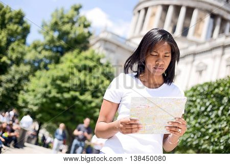 young woman reading a map in London
