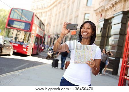 tourist taking a photo with her phone in London