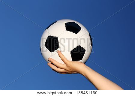 leather ball in hand with blue sky background
