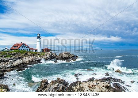 A view of the Portland Head Light following a summer afternoon rainstorm along the rocky Maine coastline.