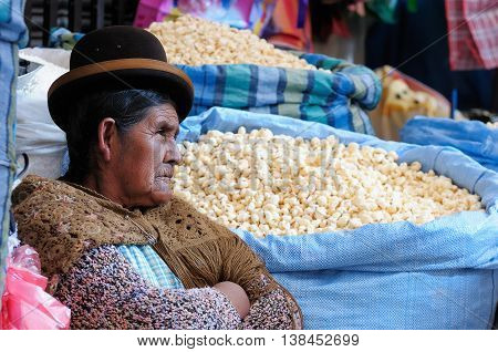 LA PAZ BOLIVIA - NOVEMBER 17: The woman in the ethnic dress is selling the corncob on steep streets of the capital city of Bolivia of the city La Paz in South America in November 17 2011