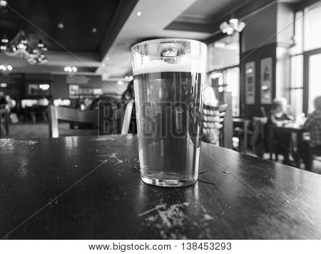 A pint of British ale beer in a pub selective focus on glass with blurred background in black and white