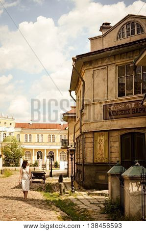 Moscow, Russia - July 13, 2013 - Antique street view on the territory of russian film studio Mosfilm. Fashion store. Walking young woman in white dress. Artistic style post processed photo.