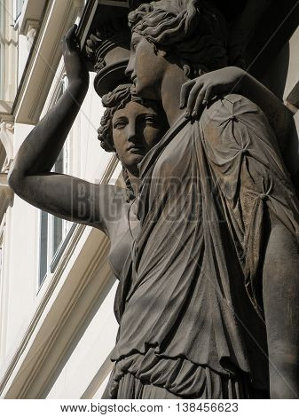 Sculpture's composition with two women in greek clothes. House in the center of Vienna, Austria. Architecture, portico, statues. Style of Ancient Greece. Beautiful faces, long combed hair, dresses.