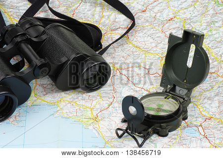 Porro binoculars and military compass lying on the map.