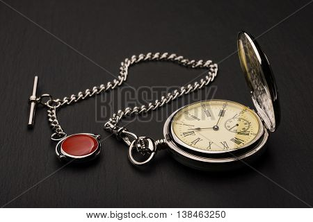 Stylish retro pocket watch on black slate background