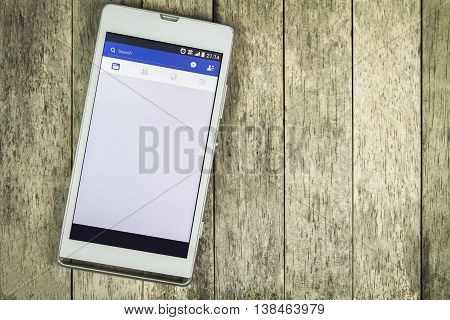 BUNG KAN THAILAND - MARCH 22 2016: smart phone display facebook app is loading new feed on wood background