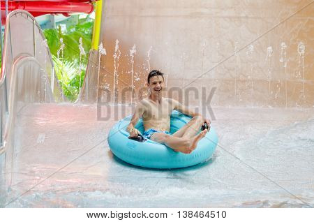 Teen boy on a inflatable tube going down a water slide