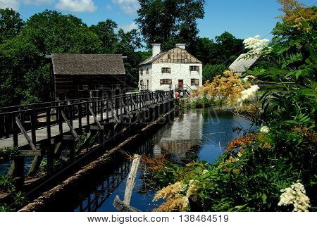 Sleepy Hollow NY - July 9 2009: Mill pond bridge grist mill and white manor house at c. 1750 Philipsburg Manor