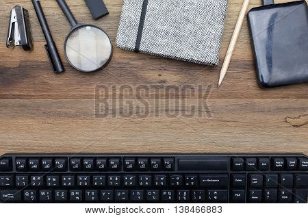 Workstation concept top view : Stapler,pen,magnifier,book,pencil,harddisk,keyboard on wooden background.In film tone