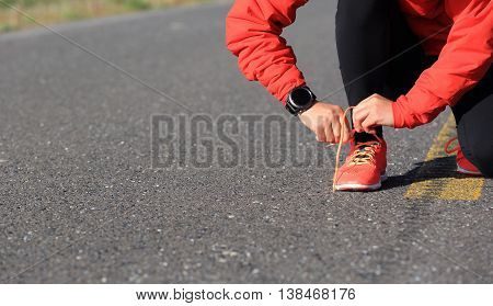 young woman runner tying shoelace on country road