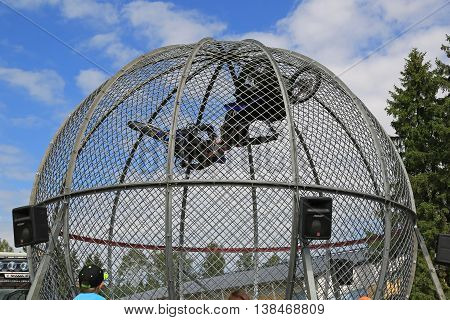PORVOO, FINLAND - JULY 2, 2016: Cage Riders Show on the annual Riverside Truck Meeting 2016. The two Finnish stunt riders Sasja Laajoki and Pasi Heikkila ride motorcycles inside a mesh sphere ball and on this moment their helmets are very close to each ot