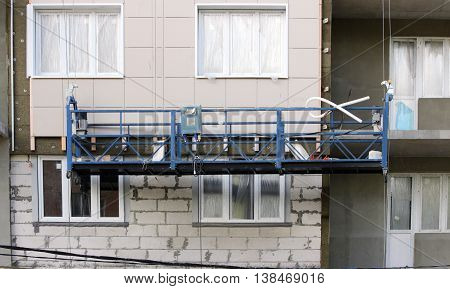 construction suspended blue cradle without workers on a newly built high-rise building