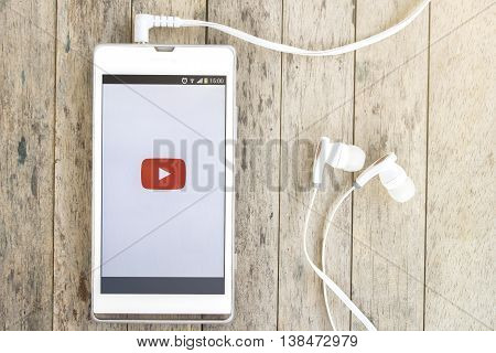 BUNG KAN THAILAND - MARCH 22 2016: smart phone display youtube app with earphones on wood background with sunlight