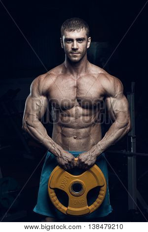Male bodybuilder fitness model trains in the gym