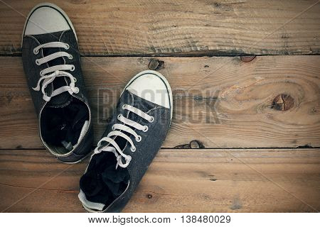 Dirty old shoes on wooden floor with copy space. Top view and Vintage effect.