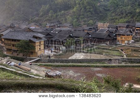 Zhaoxing Dong Village Guizhou China - April 8 2010: Countryside mountain region village of Dong ethnic minority evening spring view of tiled roofs of wooden houses and flooded rice paddies.